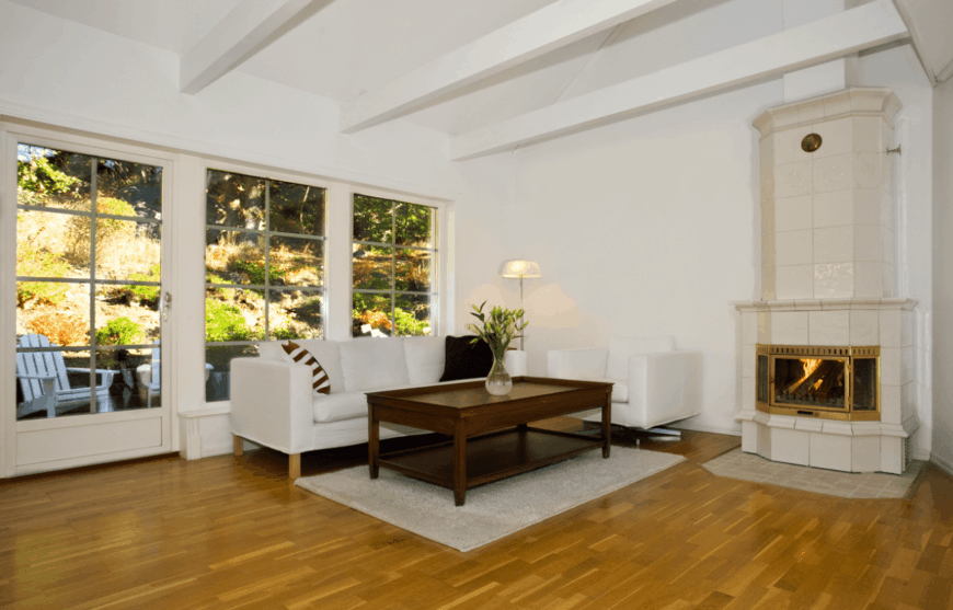 The white ceiling has exposed beams that contrast the hardwood flooring that is complemented by a gray area rug and sofa set paired with a wooden coffee table. This setup is augmented by the fireplace on the sidewall with sleek white tiles.