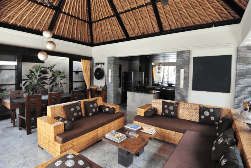The high wooden arched ceiling has black exposed wooden beams that match with the black canvas on the light gray wall as well as the black patterned throw pillows of the woven wicker sofa set surrounding the wooden coffee table.
