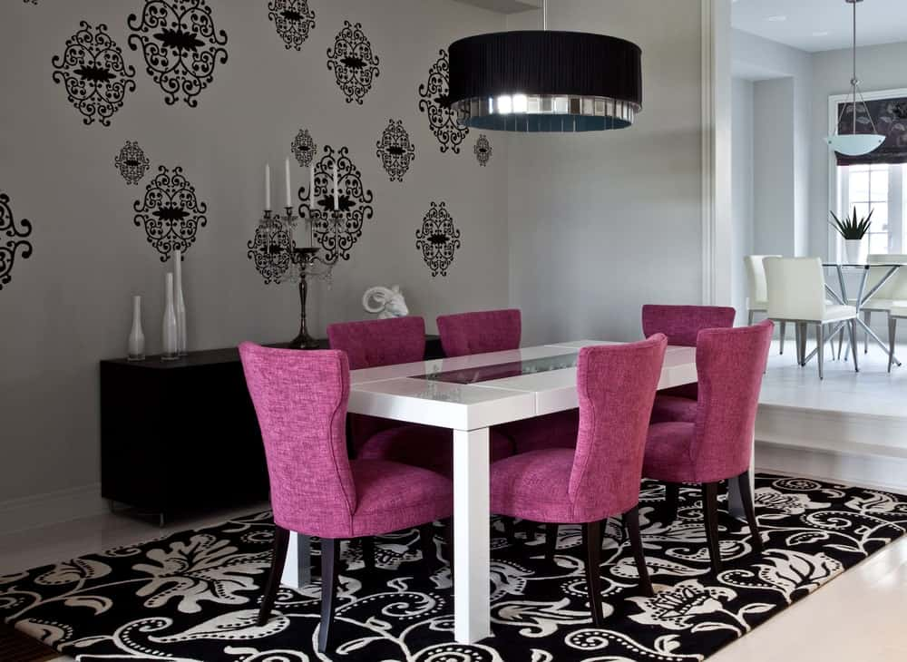 Avant garde dining room with interior wallpaper matching the area rug and a set of purple dining chairs.