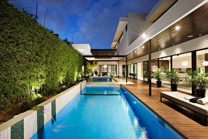 A mesmerizing pool with wooden deck hedged with gorgeous, tall bamboo grass. Beautiful potted plants can also be seen lined on the other side of the glazed house.