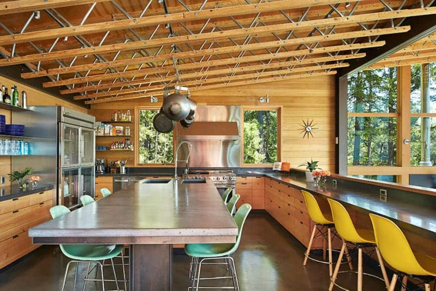 Marvelous kitchen accented with a wooden vaulted ceiling that has metal racks. It includes a huge breakfast island topped with concrete counter and fitted with two sinks. It serves as a dining table as well.