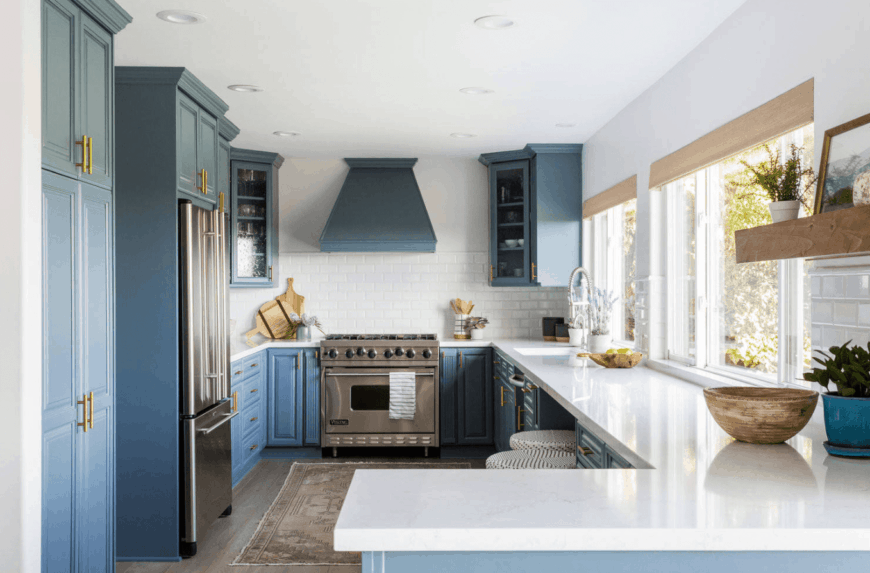 Beach style kitchen features bluish gray cabinetry and a range hood that's fixed above the white subway tile backsplash. It has white marble countertop and glass windows covered with roman shades.