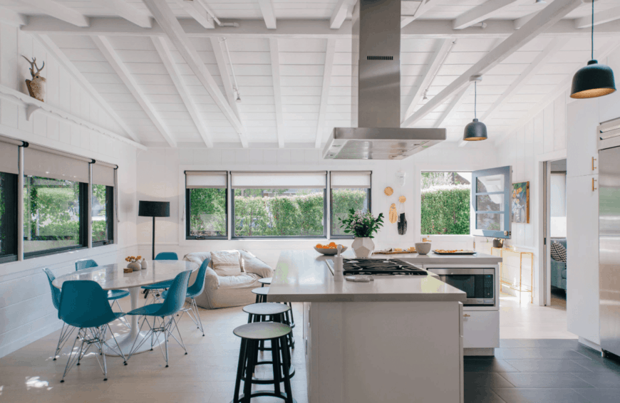 Eat-in kitchen features a vaulted ceiling with exposed white wood beams and glazed windows covered with translucent roller blinds. It has an L-shaped breakfast island with built-in cooktop and stainless steel vent hood.