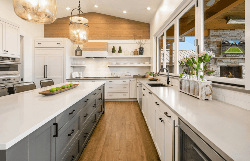 Cozy kitchen with natural hardwood flooring and wood plank accent wall. It includes a lengthy gray breakfast island topped with absolute white granite counter.