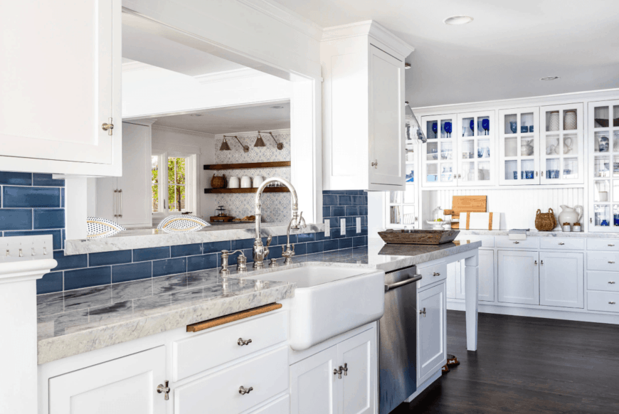 Fabulous kitchen boasts white cabinetry and gray marble countertop accented with deep blue subway tile backsplash and blue dinnerware displayed on the front glass cabinetry.