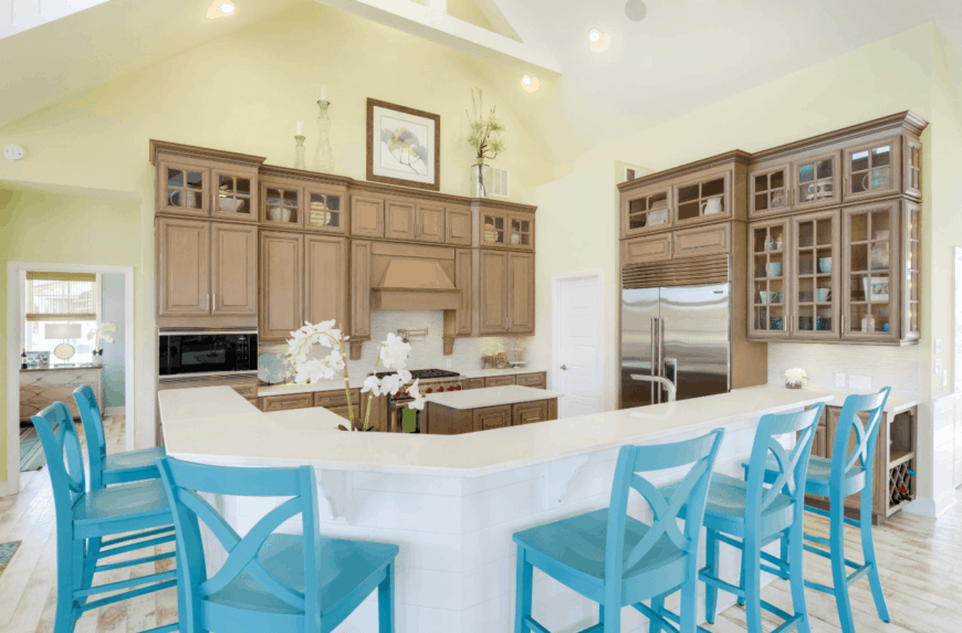 Blue counter chairs surrounded the white shiplap peninsula in this kitchen. It has pastel yellow walls and wooden cabinetry.