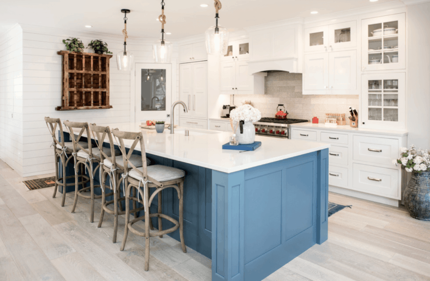 Bright kitchen features a blue breakfast island fitted with a sink and wooden counter chairs that complement with the light hardwood flooring.