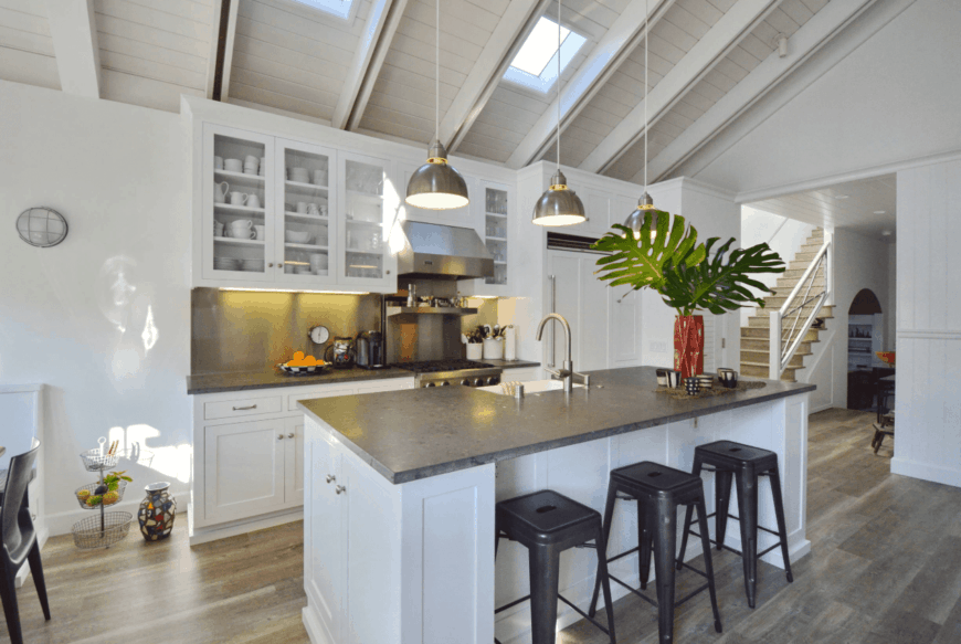 This kitchen showcases white cabinetry and breakfast island with gray countertop and bar stools. It is illuminated by pendant lights and skylights fixed on the vaulted ceiling with exposed white beams.