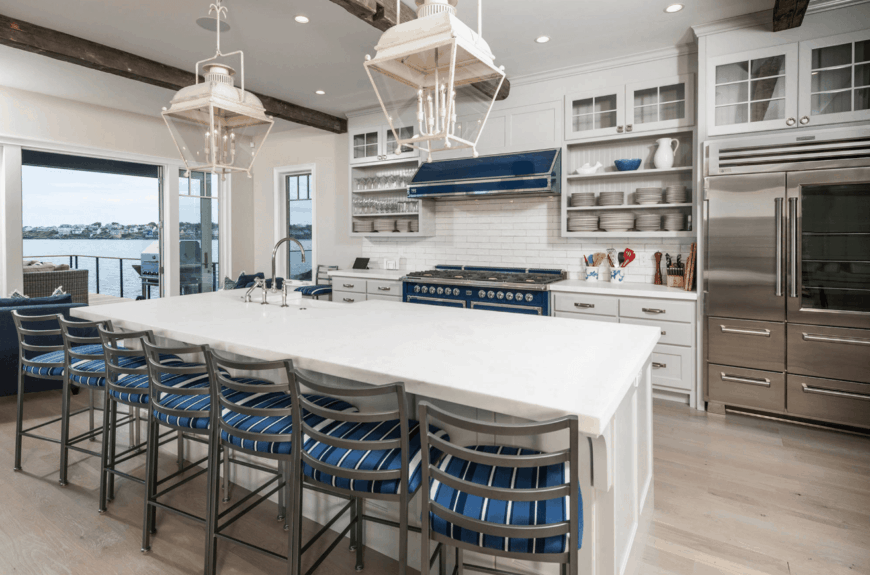 Metal chairs fitted with blue stripes cushion sit on the white breakfast island in this beach kitchen. It has light hardwood flooring and white ceiling lined with rustic wood beams.