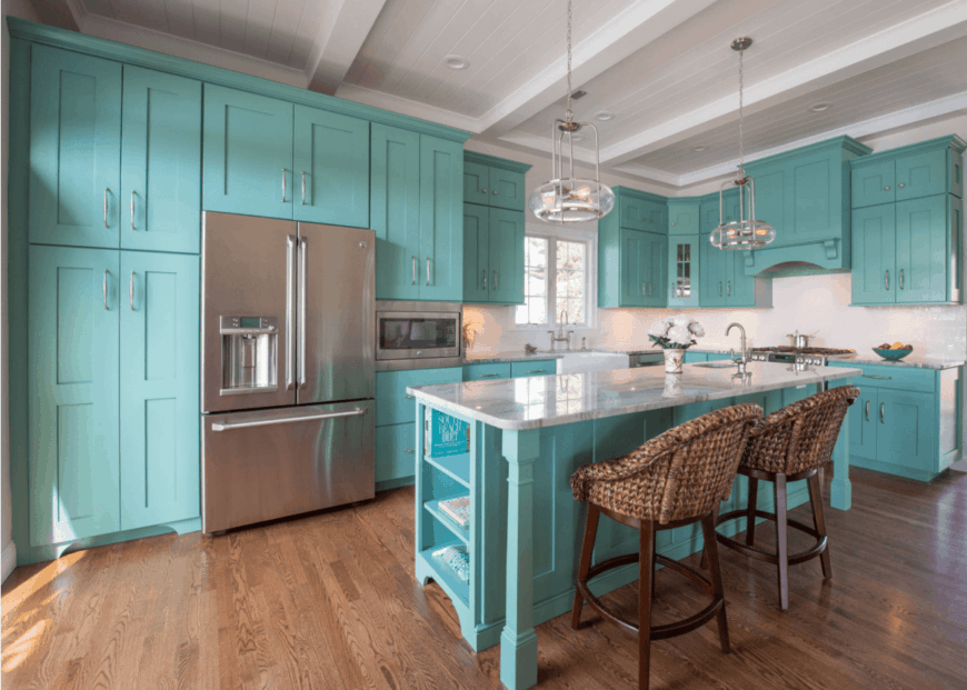 Beach style kitchen showcases aqua cabinetry that matches the breakfast island topped with white marble counter. It has built-in shelves and a pair of rattan chairs.