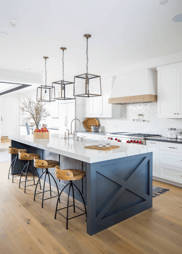 A bluish gray breakfast island stands out in this white kitchen. It is aligned with wooden bar stools and lighted by caged pendants.