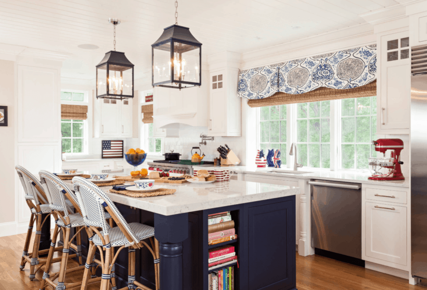 The charming kitchen offers white framed windows covered with natural woven roman shades and a blue patterned blackout lining. It includes a navy blue breakfast island topped with white marble counter and paired with white dotted chairs.