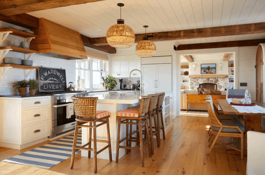 Cozy kitchen features wood plank flooring topped with a blue striped kitchen runner and white shiplap ceiling with exposed wood beams. It includes a dining space across the white peninsula surrounded with woven chairs.