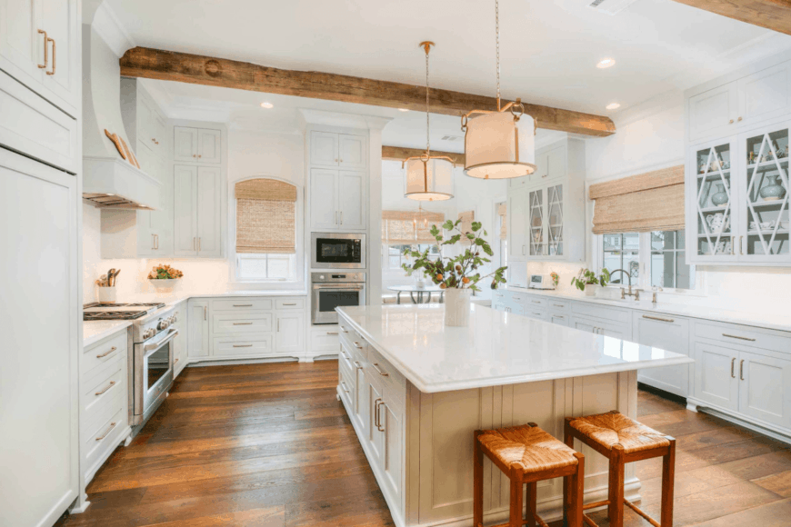 Fresh kitchen surrounded with white cabinetry that's fitted with brass knobs and pulls. It has a marble top kitchen island paired with wooden bar stools.