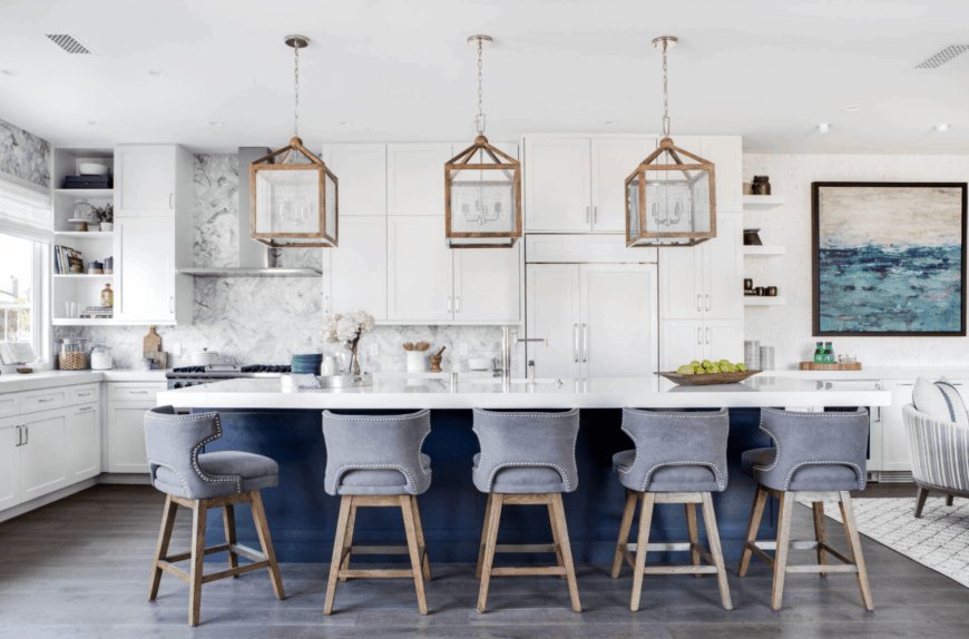 Contemporary coastal kitchen showcases a gray marble backsplash and breakfast island aligned with gray upholstered counter chairs.