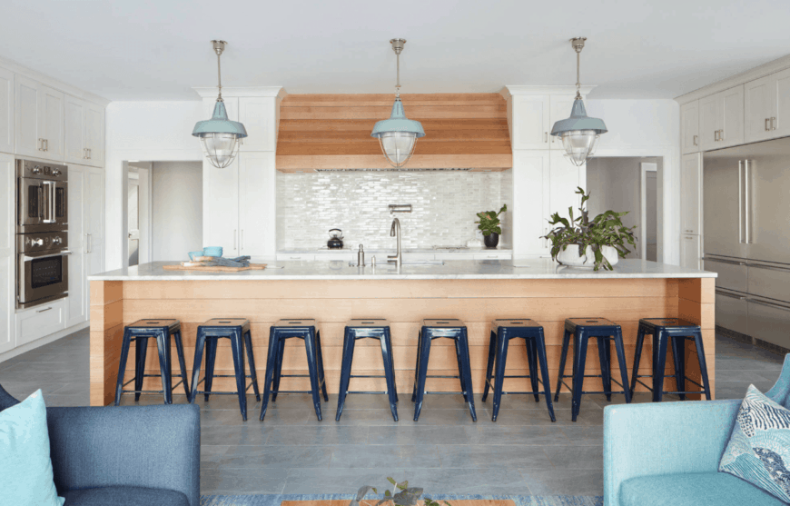 Fresh kitchen boasts a lengthy wood shiplap island bar aligned with gray stools and illuminated by huge pendant lights.