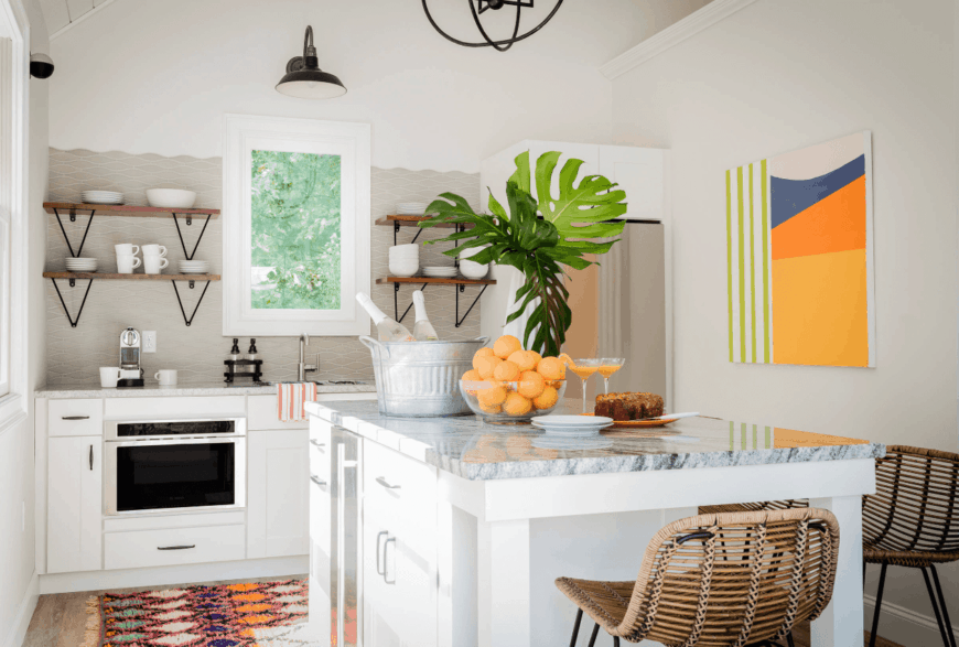 Charming kitchen designed with gray wavy backsplash tiles and colorful wall art and kitchen rug. It has a white breakfast island with gray marble countertop and rattan bar stools.