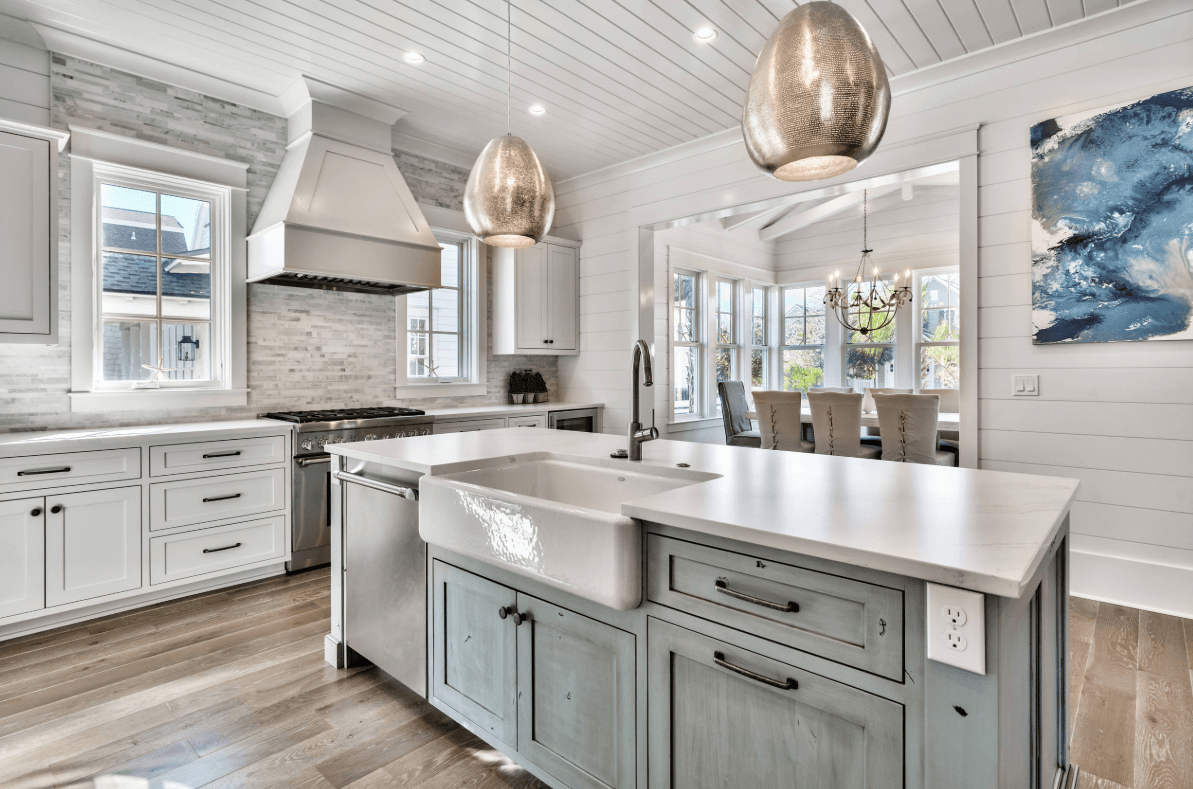 Gorgeous kitchen features a distressed light blue breakfast island fitted with an immense white sink and chrome faucet lighted by glamorous pendants.