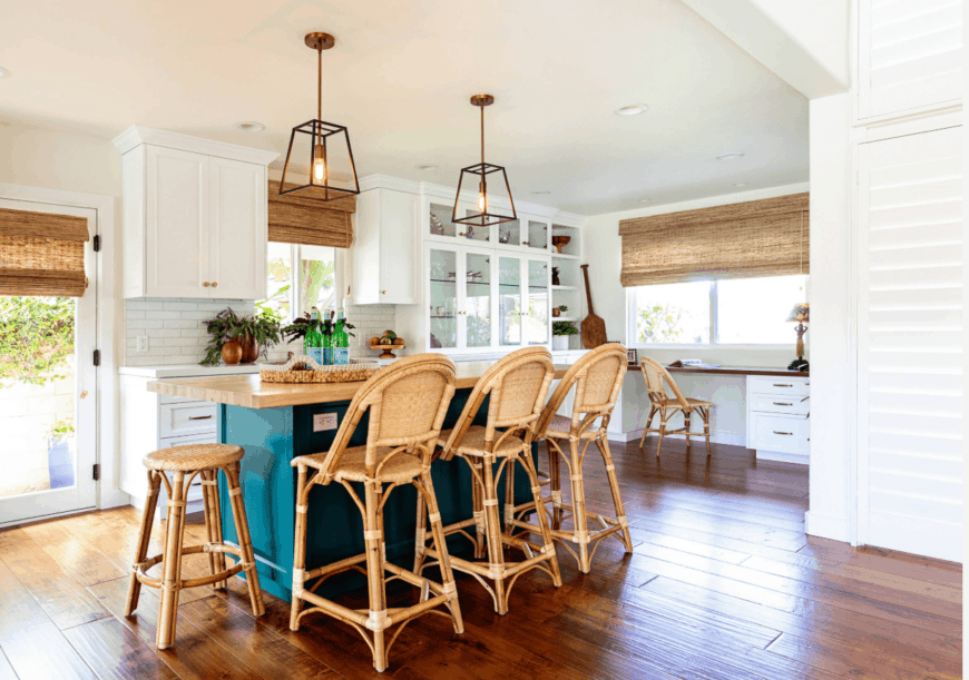 Warm kitchen illuminated by caged pendant lights and natural light from the glass windows and door. It has a vibrant teal kitchen island with a wooden countertop and rattan chairs and stool.