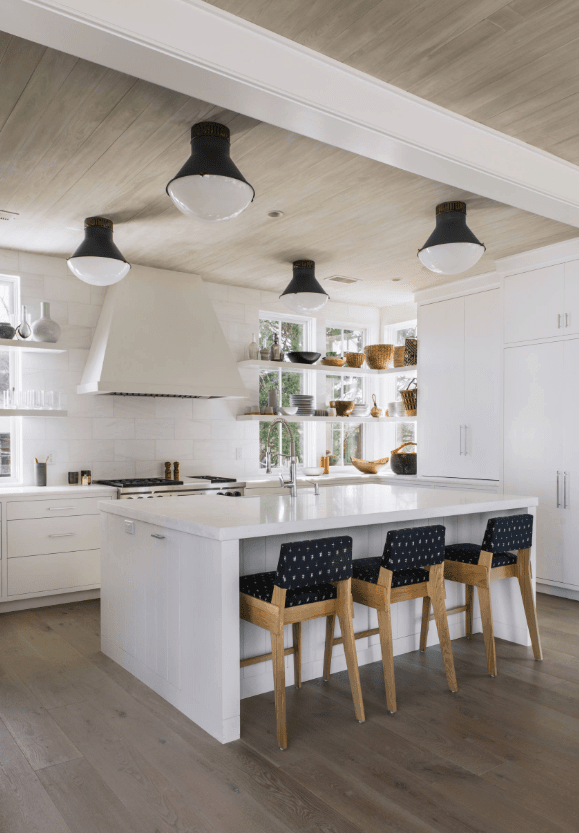 White kitchen boasts a hardwood flooring that complements with the wooden ceiling fixed with huge black bulbs.