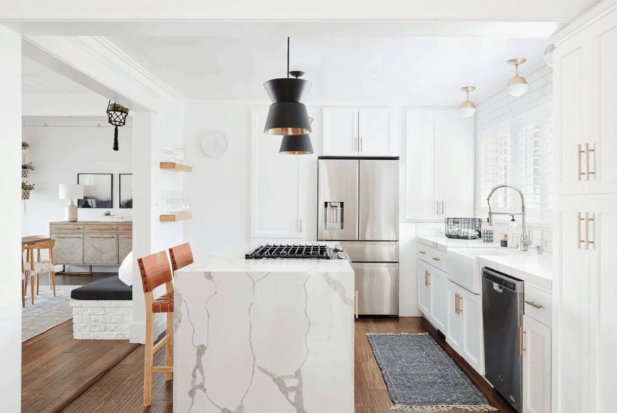 Elegant kitchen with white cabinetry and marble breakfast island fitted with a built-in cooktop and a pair of coral counter chairs.