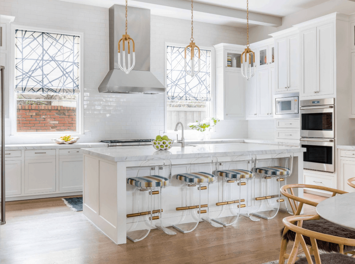 Stylish kitchen designed with lovely brass pendant lights and glass bar stools fitted with striped cushions. It has glass windows covered with translucent roman shades against subway white tile backsplash.