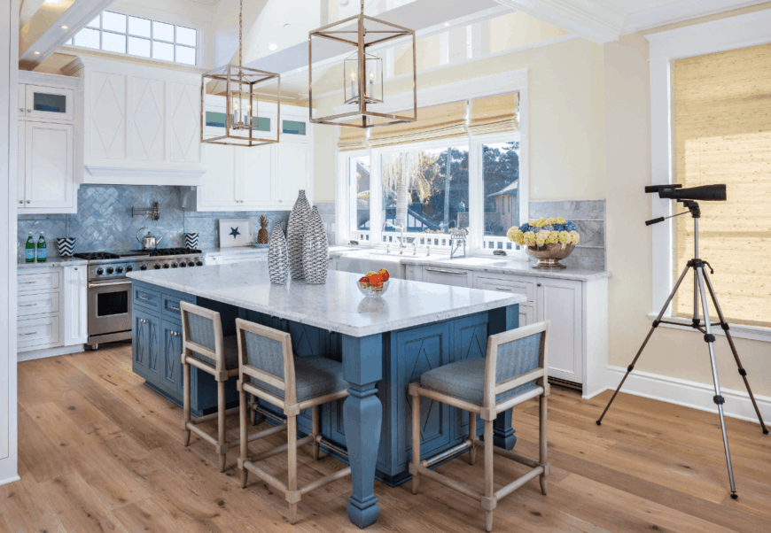 Beach style kitchen showcases a bluish gray breakfast island paired with wooden cushioned stools and topped with white marble counter styled with fancy centerpieces.