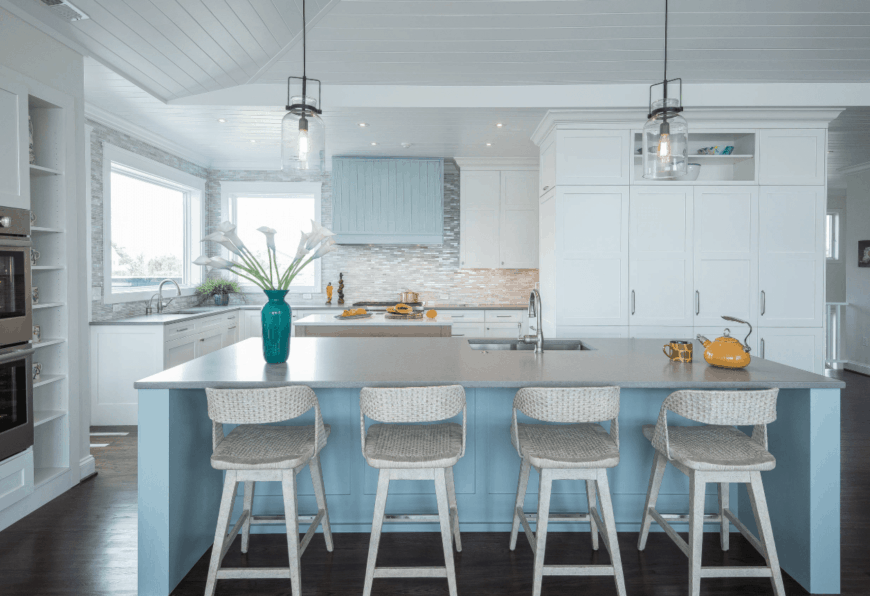 Glass pendant lights illuminated the sky blue kitchen island aligned with white rattan counter chairs in this white kitchen.
