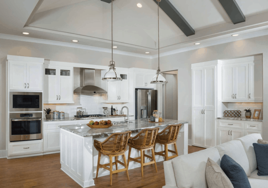 This kitchen features white cabinetry and breakfast island with gray marble countertop and rattan bar stools lighted by white pendants.