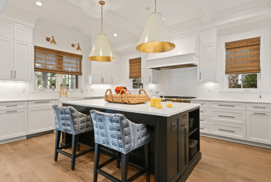 Fabulous white kitchen offers a black breakfast island illuminated by a pair of oversized brass pendants. It has white granite countertop and built-in shelves.