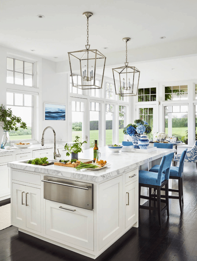 Airy kitchen surrounded with paneled glass windows overlooking a serene outdoor view. It has a white breakfast island topped with gray marble and paired with blue velvet counter chairs.