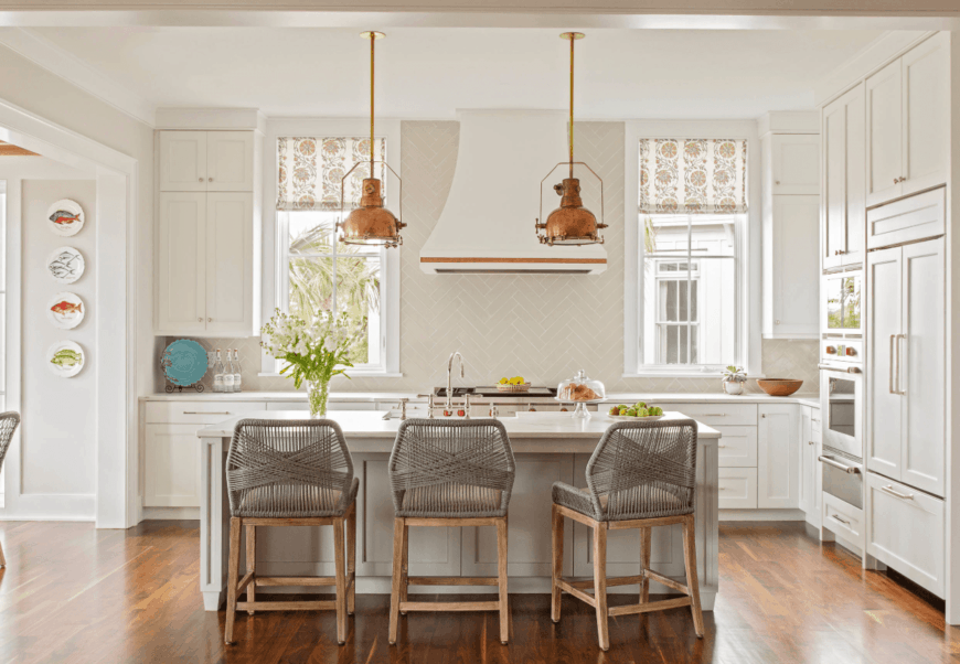 Airy kitchen styled with decorative wall plates and herringbone backsplash tiles. It includes a white kitchen island paired with gray woven chairs and lighted by rustic pendants.
