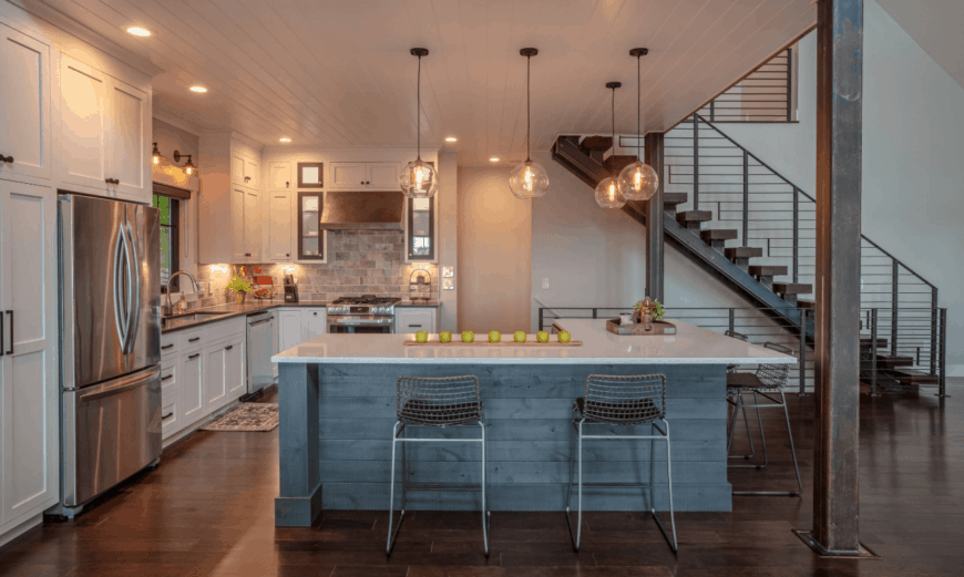 An open kitchen framed with wooden pillars that complements with the dark wood plank flooring. It has an L-shaped distressed breakfast island illuminated by glass globe pendant lights.