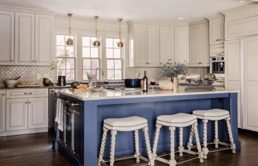 White bar stools sit on a blue breakfast island in this airy kitchen. It has white cabinetry with decorative backsplash tiles in between along with white framed glass windows.