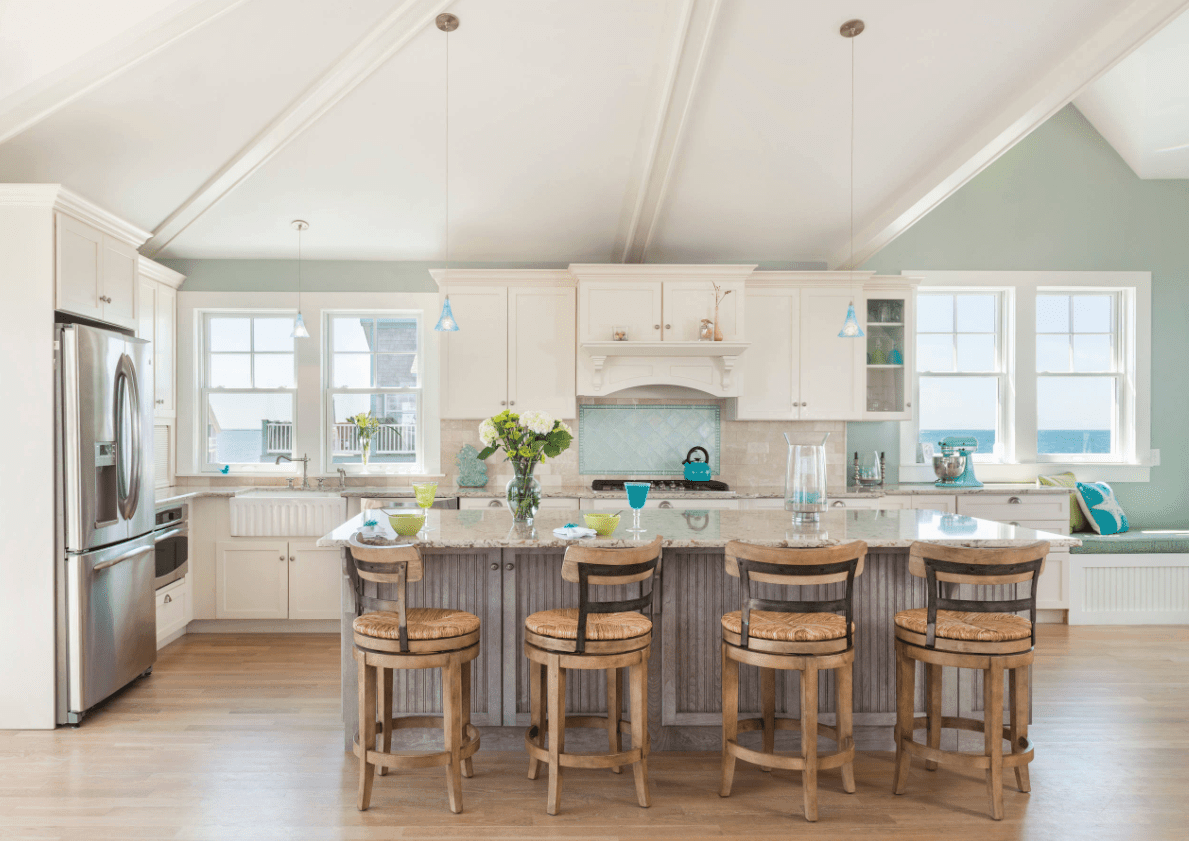 Fresh kitchen with light blue wall and gray breakfast island with wooden bar stools. It has a white seat nook fitted with light blue cushion and multi-colored pillows placed beneath the glazed window.