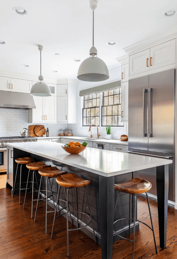 Sleek kitchen with a gray breakfast island surrounded by wooden bar stools and lighted by a pair of dome pendants. It has white cabinetry and stainless steel appliances.