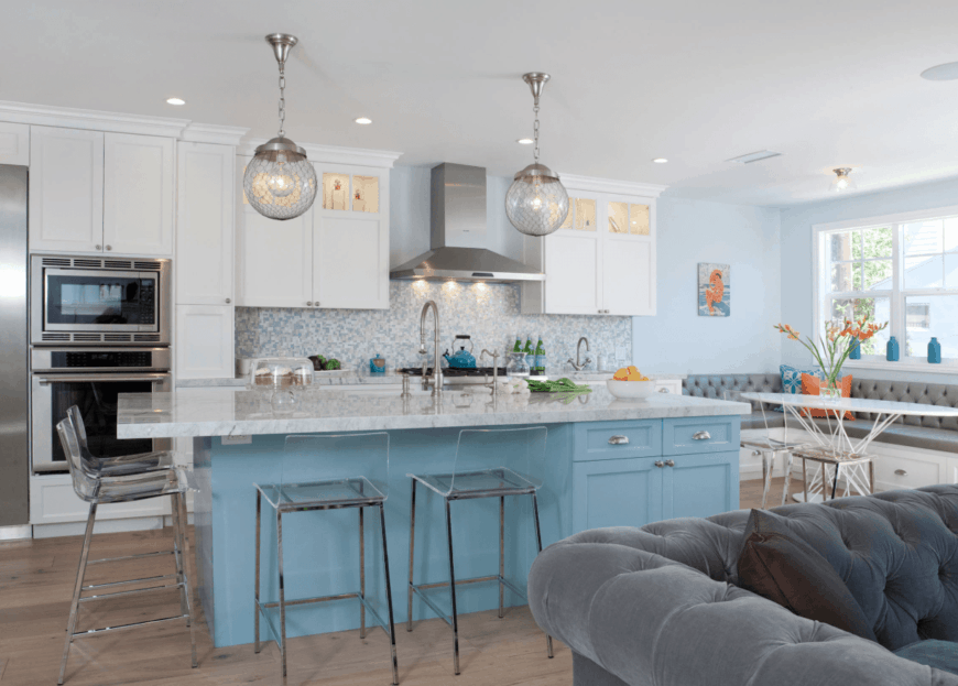 Stylish kitchen boasts a blue kitchen island and a white breakfast nook fitted with a gray tufted cushion and accented by blue and orange pillows. It is paired with an oval table and glass chairs that match the bar stools.
