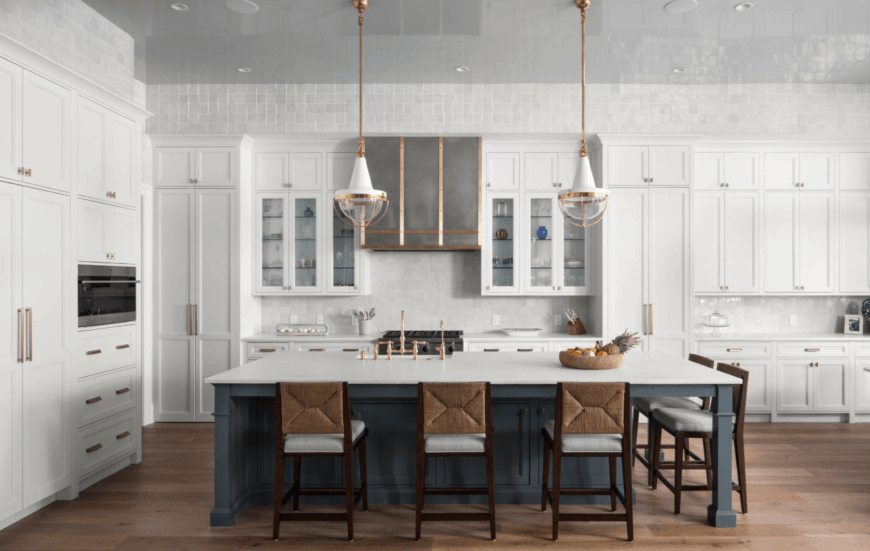 Modern kitchen showcases white cabinetry with brass knobs and pulls that complements with the pendant lights that hung over a bluish gray kitchen island.