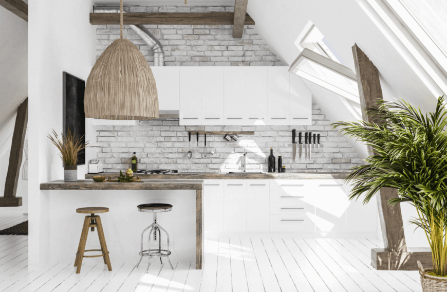 Barn kitchen with white brick backsplash tile against a vaulted wall fitted with a glass window. It includes a white peninsula with a wooden countertop and mismatched counter chairs.