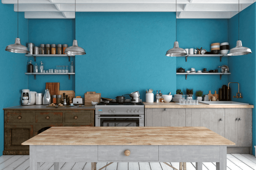 Beach style kitchen features blue wall and distressed white wood plank flooring. It has a wooden breakfast island lighted by stainless steel pendants.