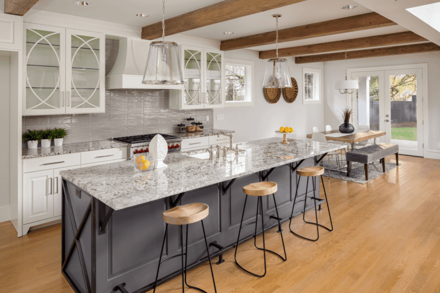 The magnificent kitchen offers a dining space with a wooden table and tufted bench along with white chairs that sit on a gray rug. It has a gray kitchen island topped with marble counter.