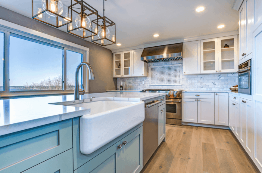 Bright kitchen features white and aqua cabinetry topped with white marble counter and gray subway tile backsplash.