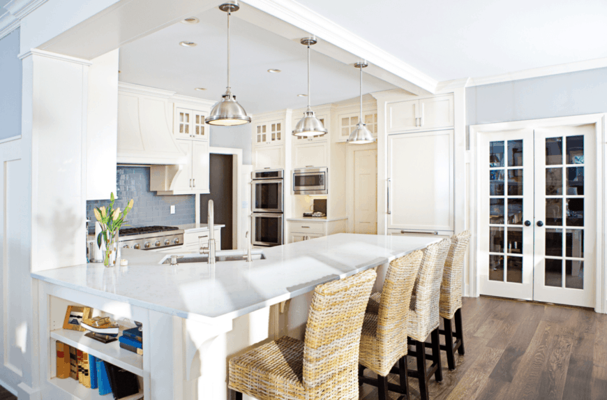 Yellow rattan chairs sit on a white peninsula with built-in shelves and marble countertop. It is illuminated by aluminum pendant lights that hung from a white ceiling beam.