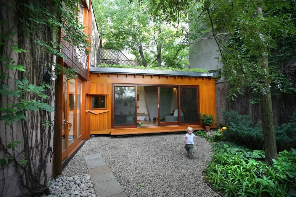 This part of the house is covered with wood planks and sliding doors that open to the yard filled with stones.