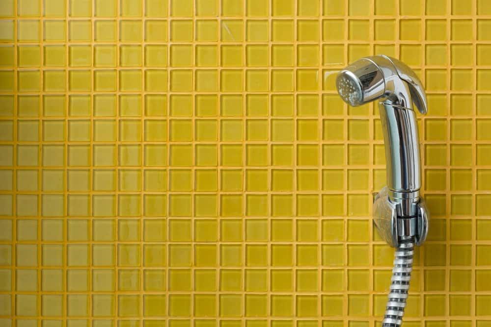 Bidet spray against a yellow tile wall.