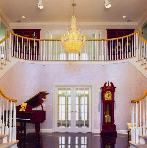 Bifurcated staircase designed with a blush patterned wallpaper along with a grandfather clock and piano. It is fitted with a french door and lighted by a lovely chandelier.