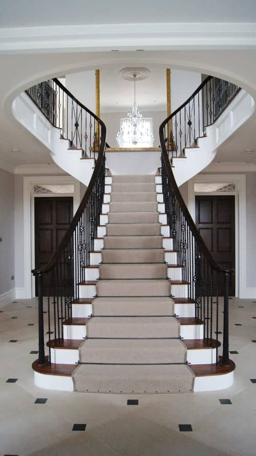 Traditional staircase features ornate iron spindles topped with dark wood handrails. It has wooden treads against white risers with a running gray carpet.
