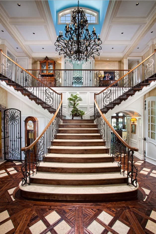 A vintage chandelier that hung from a coffered ceiling lighted the grand foyer staircase. It has wrought iron balustrade fitted on the steps that complement the hardwood flooring.