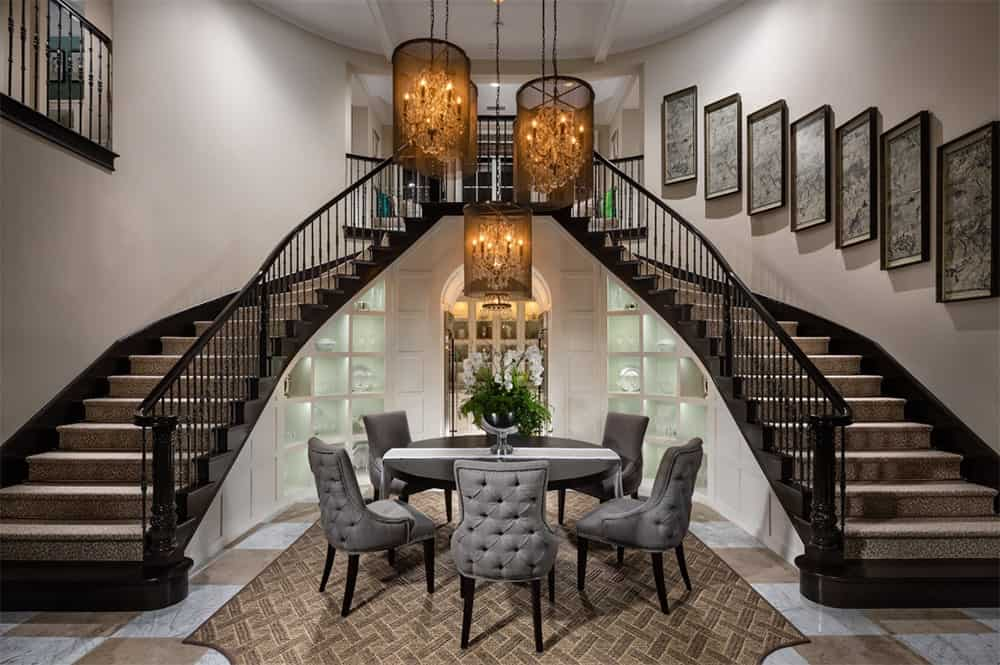Transitional staircase decorated with wall art frames mounted on the white wall and built-in shelves with displayed dinnerwares underneath. It is accompanied by a black round table surrounded with gray tufted chairs.