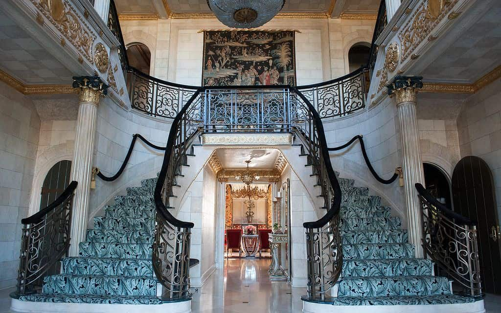 Bifurcated staircase with ornate balustrade and a pair of classic gilded columns fixed to stone brick walls. It is accented by an elegant carpet running on the treads.